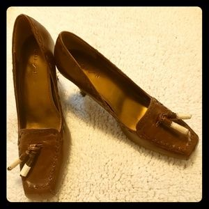 Brown Leather pumps with tassels still wrapped.
